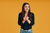 Surprised young woman in casual clothing using keeping hands together