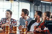 Cheering young men in casual clothing enjoying beer