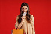 Beautiful young woman in casual clothing carrying shopping bag and credit card