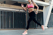 Confident young woman in sports clothing running