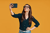 Happy young woman in casual clothing taking selfie and puckering