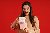 Surprised young woman in casual clothing holding a present
