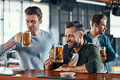 Group of cheerful young men in casual clothing enjoying beer and communicating
