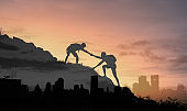 People helping each other up a mountain overlooking a city.