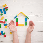 Directly above on wooden colorful bricks on a white wooden background. Hands of a man protect a house assembled from multi-colored wooden blocks. Home, family and education concept.