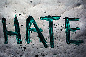 The word hate painted by green paint on metal table