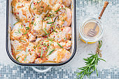 Top view of seasoning chicken legs with herbs and honey