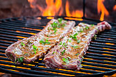 Spicy ribs with thyme and spices on grill with fire