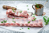 Closeup of seasoning ribs with herbs and marinade