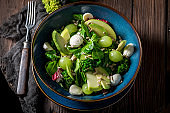 Healthy kale salad made of avocado, lettuce and fruits.