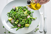 Healthy green salad made of spinach, radishes and olive oil.