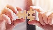 Businessman hand connecting jigsaw puzzle.Business solutions, success and strategy concept.