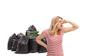 Disgusted woman closing her nose in front of a waste bin