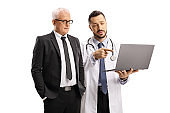 Male doctor holding a laptop and talking to a mature businessman