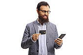 Bearded man with a credit card smiling and looking at a mobile phone