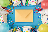 Top view photo of birthday party composition closed craft paper envelope in the middle spiral candles pipes straws hats balloons confetti paper cups and plates on isolated blue wooden table background