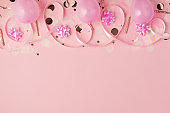 Top view photo of birthday composition with pink ribbon stars balloons golden taper candles serpentine and confetti on isolated pastel pink background with copyspace