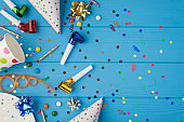 Top view photo of birthday party composition spiral cocktail tube ribbon stars candles pipes hats confetti polka dots paper cup plate isolated blue wooden table background with copyspace on the right