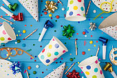 Top view photo of birthday party composition spiral cocktail tubes multicolored ribbon stars striped candles pipes hats confetti polka dots paper cups and plates isolated blue wooden table background