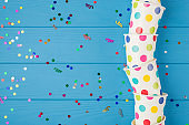 Top view photo of birthday party composition confetti and polka dots paper cups on the right on isolated blue wooden table background with copyspace on the left
