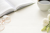 Photo of white cup of coffee spectacles flowers and open book on white table with copyspace