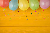 Overhead photo of multicolored rainbow confetti and balloons isolated on the yellow wooden background with blank space