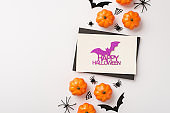 Top view photo of black envelope glitter purple bat inscription happy halloween on white card pumpkins spiders web and bats silhouettes on isolated white background with copyspace
