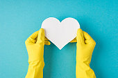Top view photo of hands in yellow rubber gloves holding white paper heart on isolated pastel blue background with copyspace