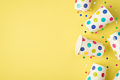 Above photo of cups drink soda and multicolored confetti isolated on the yellow background with empty space