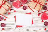Top above overhead close up view photo of st valentines day composition with giftboxes and sheet of blank paper for text writing with red envelope