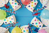 Top view photo of birthday party composition spiral candles pipes striped straws hats balloons confetti polka dots paper cups and plates on isolated blue wooden table background with copyspace