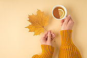 First person top view photo of female hands in yellow sweater holding yellow autumn maple leaf and cup of tea with lemon slice on isolated pastel orange background