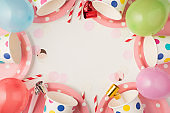 Overhead photo of cups plates party tubules whistle and balloons isolated on the white background with blank space