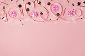 Top view photo of birthday composition with pink ribbon stars golden taper candles serpentine and confetti on isolated pastel pink background with copyspace