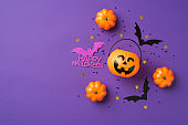 Top view photo of halloween decorations pumpkins basket black sequins golden stars bat silhouettes and purple inscription happy halloween on isolated violet background with copyspace