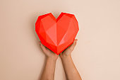 children's hands hold red heart against a beige background.  top view, flat lay. St. Valentine's comcept. Copy space. Mom's Day