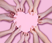 Group of people hands of adults and children holding a pink heart icon against a pink background. monochrome.