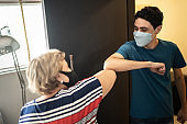 Grandmother greeting grandson with elbow bump at home - wearing face mask