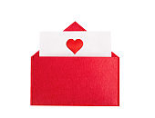 Red open envelope with a sheet of paper with a heart on a isolated background with copyspace. Valentine's day holidays concept and love notes, christmas and new year  letters for Santa Claus