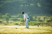 Golfer sport course golf ball fairway. People lifestyle man approach playing game golf tee of on the green grass. Asian man player game shot in summer. Healthy and Sport outdoor
