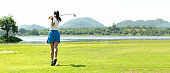 Golfer sport course golf ball fairway. People lifestyle woman playing game golf and hitting go on green grass river and mountain background.