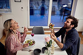 A young couple having a good time while eating together. Home, kitchen, meal, relationship