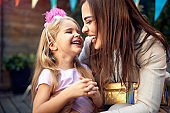 beautiful little girl giggling in a hug of a young female adult  birthday party. close relationship, love, positive emotions concept