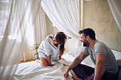young beautiful couple laughing early in the morning in the bedroom. morning, adults, satisfied, joy,  concept
