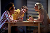young / multiethnic group of friends socializing, having fun, laughing, drinking wine, sitting at the table