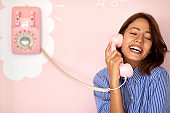 A beautiful young girl talking on a retro looking telephone hanging on the wall in a pastry shop. Pastry shop, ambience