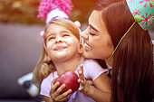 Girl  celebrate birthday and  eating fruit with her mother.