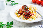 Spaghetti pasta with meatballs in tomato sauce and herbs on white plate. Comfort food concept.