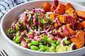 Vegan salad bowl with baked sweet potato, edamame beans, nuts and pink beetroot dressing. Vegan food concept.