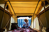 Travel woman sitting in the auto tent and enjoying outdoors from the window with amazing landscape. Best wake up during adventure trip with feeling. Concept of nature and having freedom in holiday